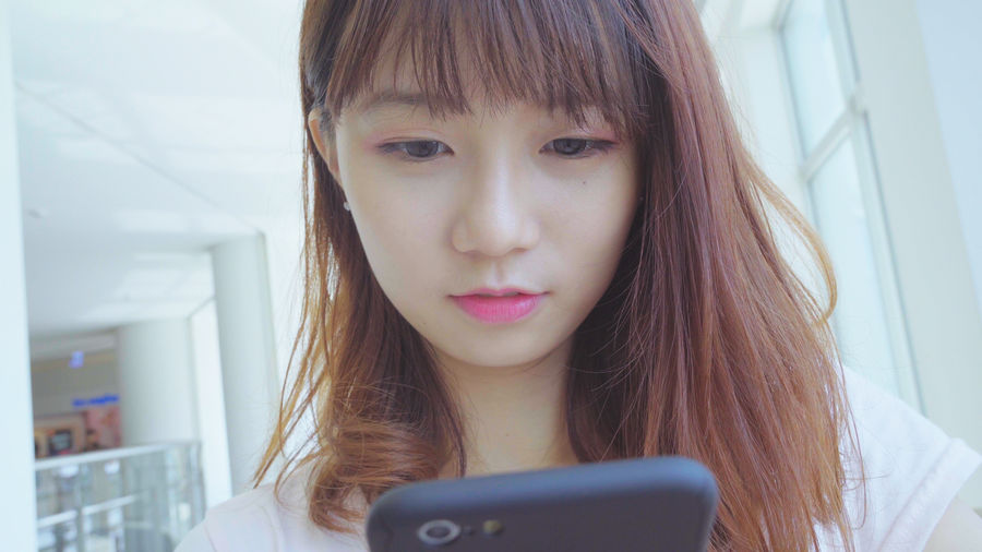 Close-Up Of Young Woman Using Mobile Phone In Shopping Mall