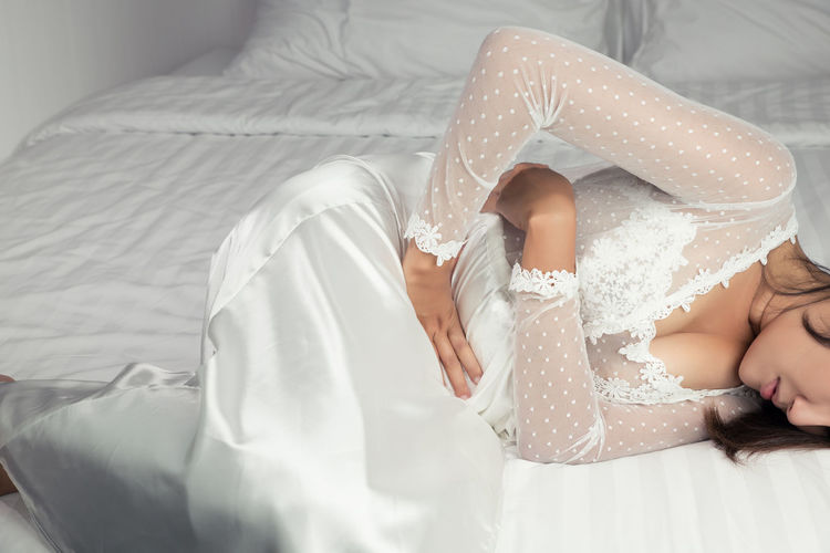 Low section of woman with stomachache lying down on bed