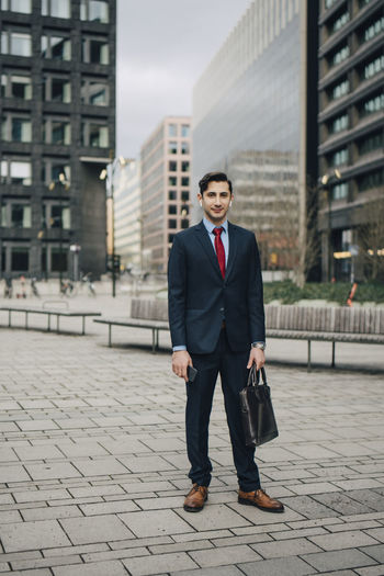 Full length portrait of young man in city