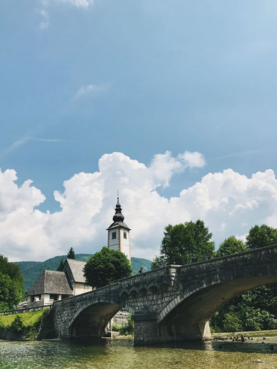 Arch bridge over river against cloudy sky