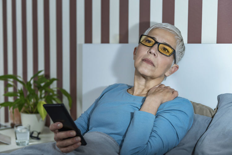Senior woman with blue-light blocking glasses lying in bed before sleeping, using smartphone.