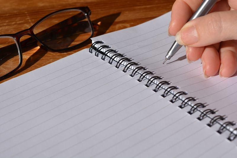 Close-up of woman writing on blank spiral notebook