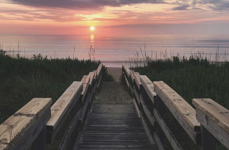 Boardwalk Beach Sunrise Sunset Sky Sea Beauty In Nature The Way Forward Horizon Over Water Nature Water Direction Horizon Cloud - Sky Scenics - Nature Tranquil Scene No People Sunlight Orange Color Tranquility Railing Sun Outdoors