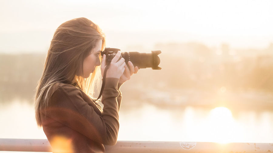 Side view of woman photographing against clear sky
