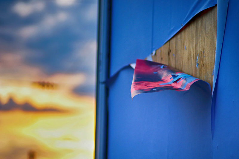 Close-Up Of Torn Paper On Window During Sunset