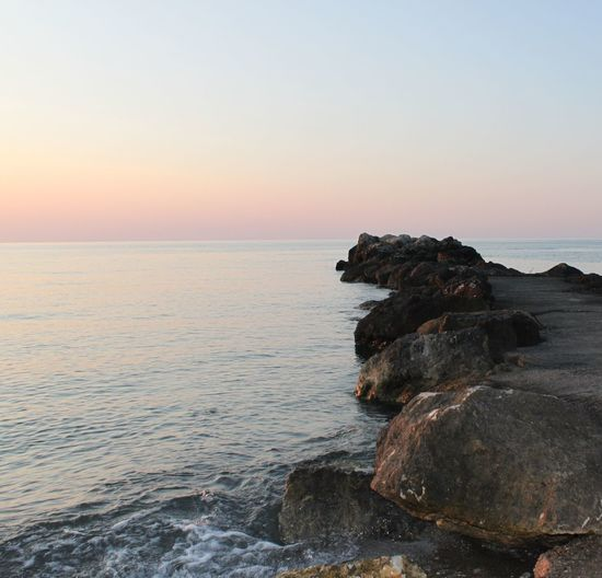 Scenic view of sea against clear sky at sunset