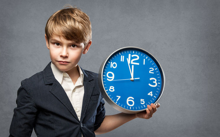 Serious 7 Year old Boy, Holding a blue Big Clock, just minutes before midnight: either, he is warning us that time is running out, or ready to celebrate New Year 7 Years Old Kids New Year Boy Business Child Clock Clock Face Concrete Cute Environment Midnight New Years Eve One Person People Portrait Studio Shot Suit Ticking Time Urgency Warning