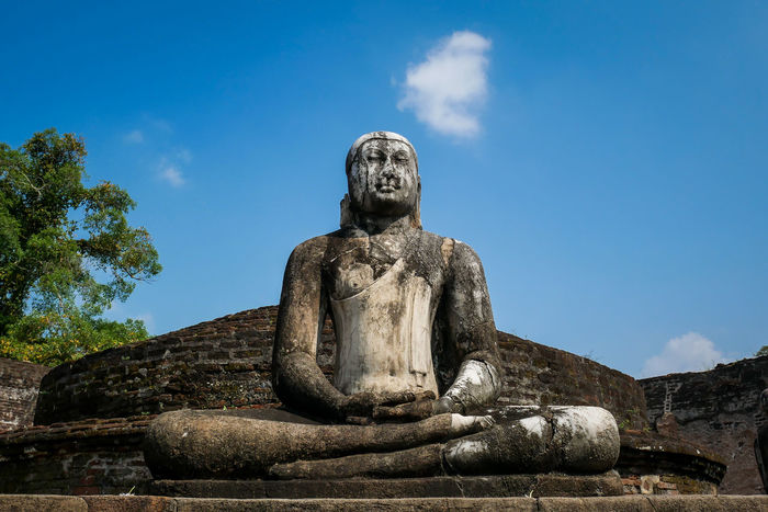 Sitting Buddha made of stone against blue sky in Sri Lanka Ancient Ancient Civilization Architecture Blue Sky Buddha Buddha Statue Buddhism Buddhist Contemplation Meditating Meditation No People Old Outdoors Peace Religion Rock Silence Sky Sri Lanka Statue Statue Stone Temple