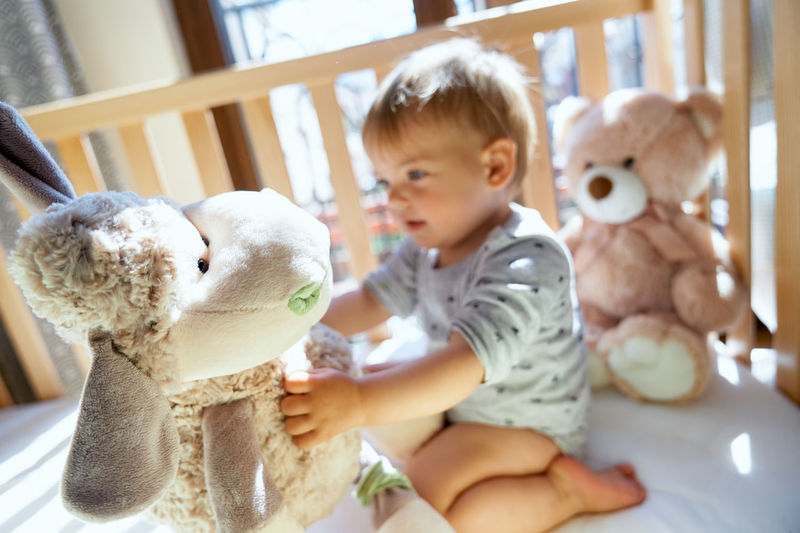 Cute girl holding toy sitting in crib