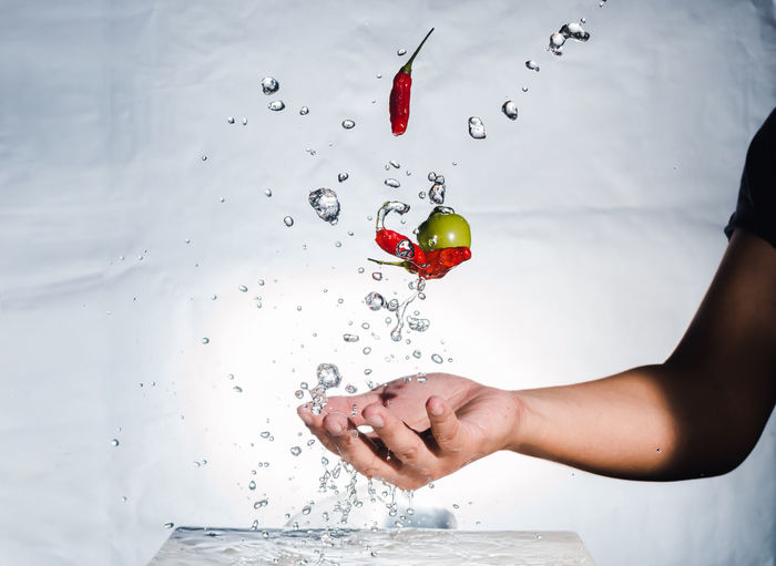 Close-up of hand splashing water with red chili peppers and olive