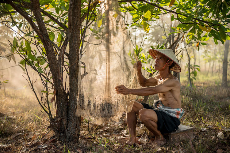 Shirtless senior man drying fishing net at forest