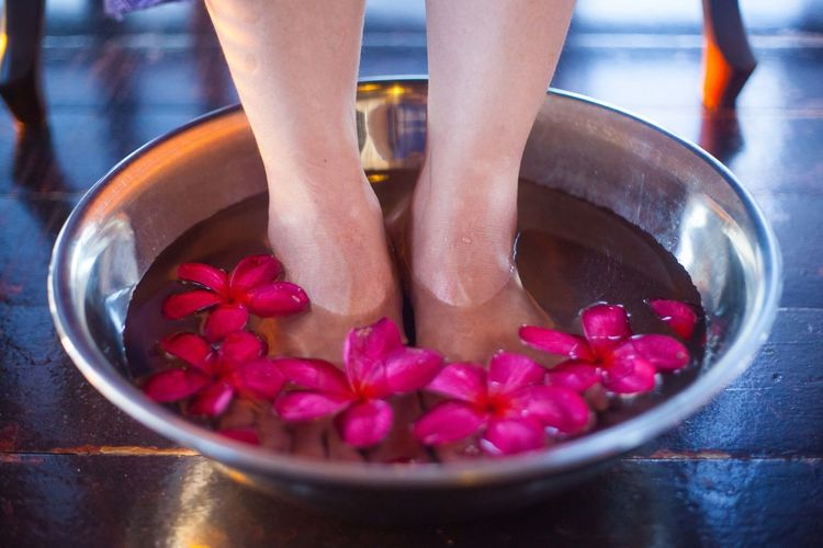 Low section of woman soaking feet amidst flowers in water bowl at health spa