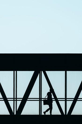 Silhouette people walking on bridge against clear sky