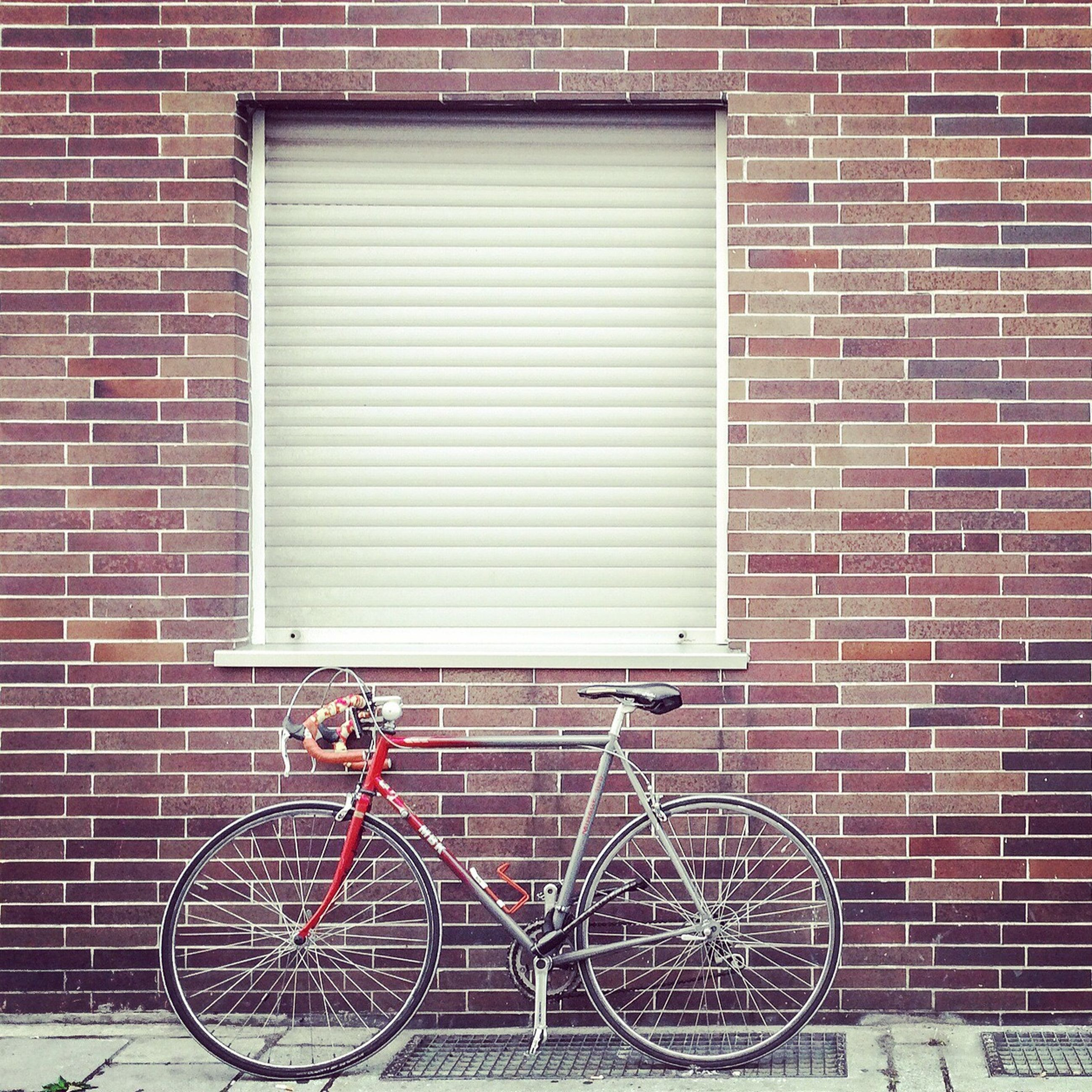 bicycle, building exterior, architecture, built structure, brick wall, stationary, wall - building feature, parked, transportation, parking, mode of transport, land vehicle, window, wall, metal, house, day, building, no people, leaning