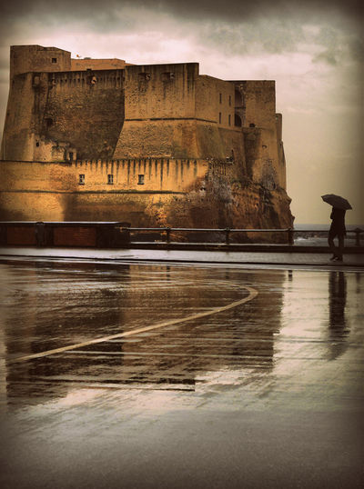 A passer by with an umbrella in front of the castle (Naples, Italy) Water Architecture Built Structure Building Exterior Reflection Sky Waterfront Nature Building Travel Destinations The Past History Travel Tourism Outdoors Lake Auto Post Production Filter Day Castle Castle Castel Dell'ovo Rain Pioggia Naples Napoli