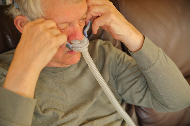 High Angle View Of Senior Man Breathing With Oxygen Mask While Sitting On Sofa At Home