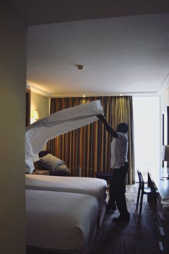 Housekeeper Making Bed In Hotel Room