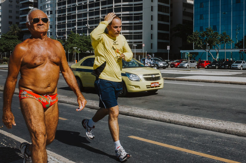 Jogger and fit old guy in speedo walking at the street in Rio de Janeiro, Brazil Taxi Fitness Healthy Lifestyle Jogging Running Streetphotography Rio De Janeiro Documentary Photography Brazil Hot Weather Cool Leisure City Full Length Men Togetherness Standing Building Exterior Moving Street Scene Road Street My Best Photo
