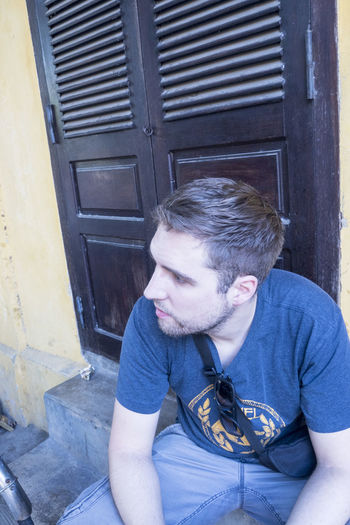 Portrait of young man sitting at entrance of building