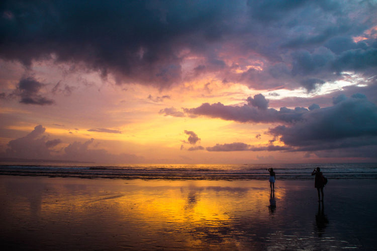 Women standing at beach against sky during sunset
