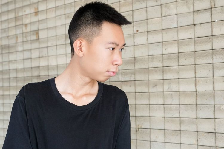 Close-up of young man looking away against wall