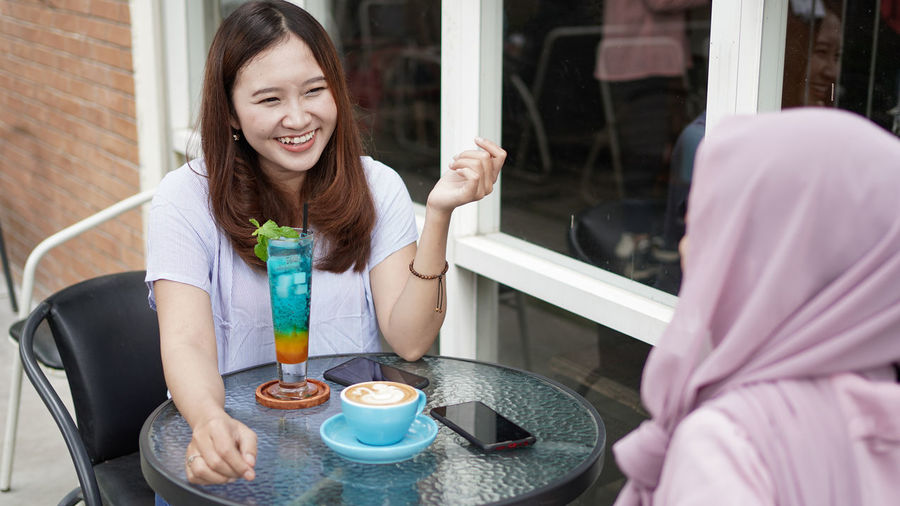 Portrait of smiling woman holding coffee while sitting on table