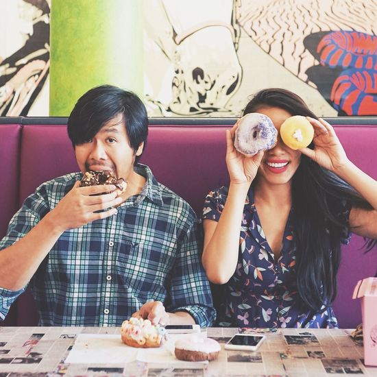 Portrait of man eating donut with woman at restaurant