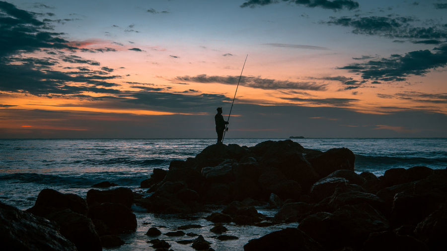 SCENIC VIEW Of Man Fishing At Sunset