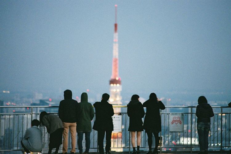 Rear View Of People Looking At Illuminated Tokyo Tower Against Sky
