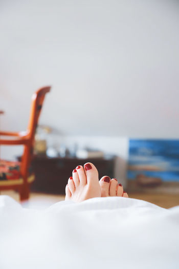 Low section of woman relaxing on bed against wall at home
