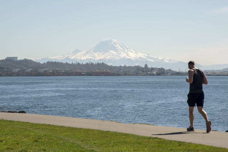 Runner on Seattle waterfront with snow and glacier covered Mount Rainier in the distance. Mountain Full Length Rear View Scenics - Nature Beauty In Nature Standing Water One Person Sky Nature Day Real People Leisure Activity Land Casual Clothing Lifestyles Women Tranquility Mountain Range Outdoors Mountain Peak Mount Rainier Volcano Healthy Lifestyle Runner Jogger Sweaty Sweat Athlete Climate Change Global Warming Stride Puget Sound Elliott Bay Salish Sea