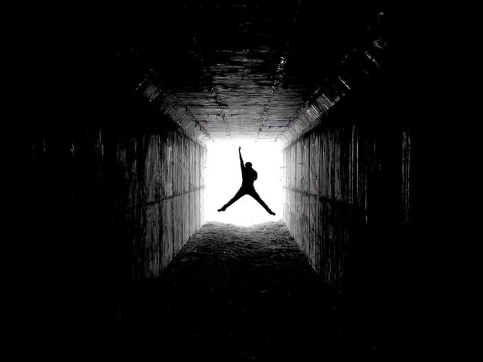 Silhouette Man Jumping With Arm Raised In Tunnel