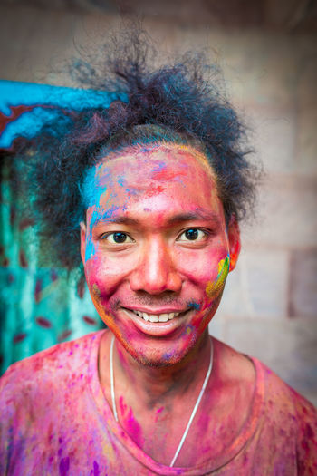 Portrait of young man covered with powder paint during holi