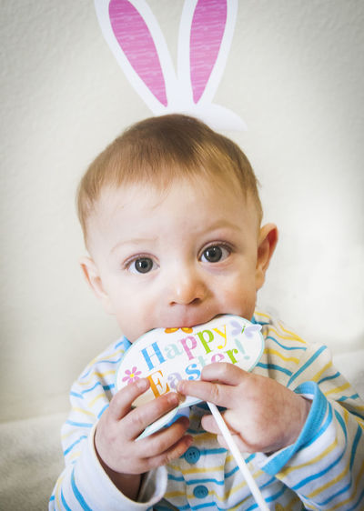 Optical illusion of baby boy with rabbit ears biting toy against wall