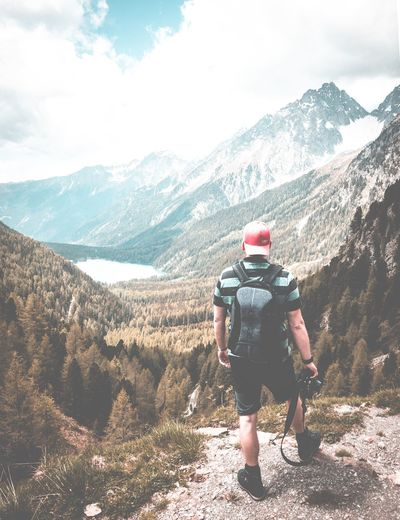 Rear view of man skateboarding on mountains against sky