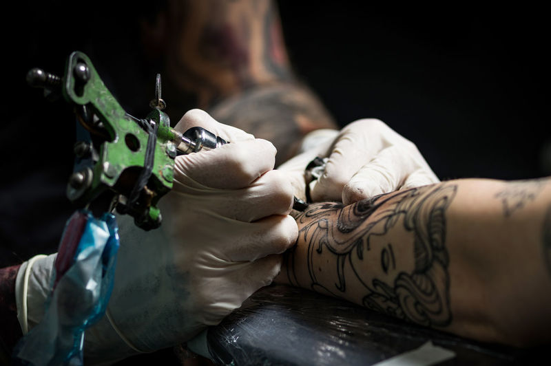 At Work Pain Tattoo Artist Adult Art And Craft Artist Close-up Creativity Day Expertise Human Body Part Human Hand Indoors  Ink Men Occupation People Protective Glove Real People Skill  Suffering Tattoo Tattooing Two People Working