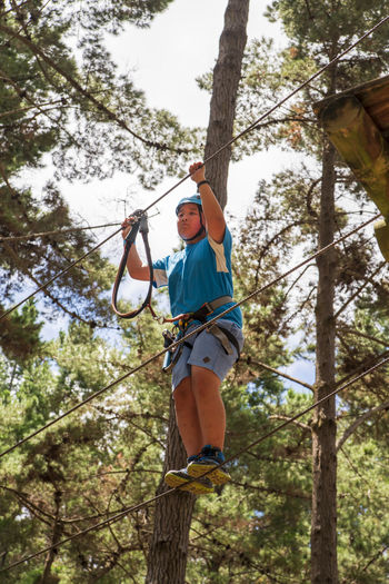 Low angle view of man climbing on rope in forest