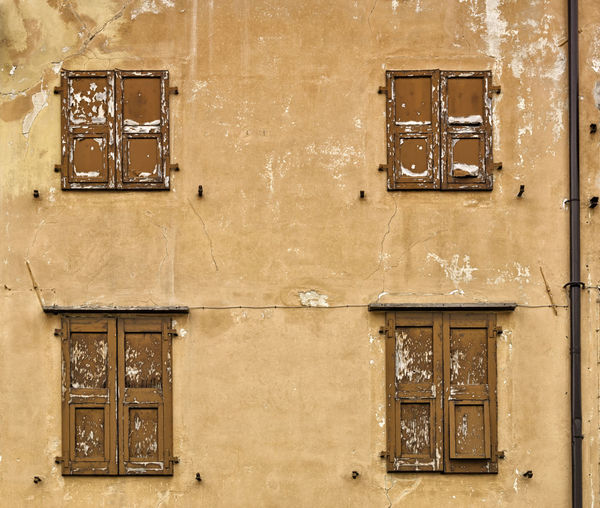 An old Italian rugged building facade with cracks and ruined wooden blinds. Traditional old Italian architecture style. Grunge uneven orange background City Construction Cracks Home Rugged Udine Wall Architecture Blinds Building Cement Complex Concrete Facade Building Front Grunge House Housing Italian Italy Old Structure Urban Vintage Window
