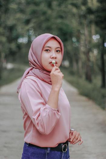 Portrait of woman wearing hijab eating lollipop