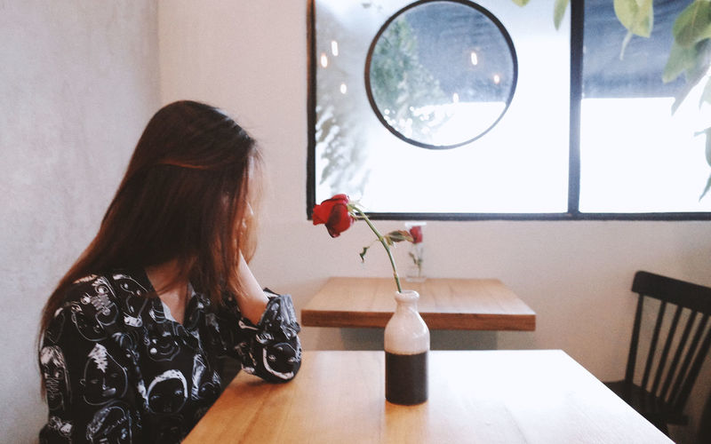 One Person Real People Indoors  Long Hair Women Lifestyles Hairstyle Hair Sitting Flower Adult Rear View Leisure Activity Flowering Plant Casual Clothing Young Women Table Lighting Equipment Seat Electric Lamp