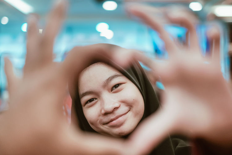 Portrait of smiling teenager making heart shape with hands