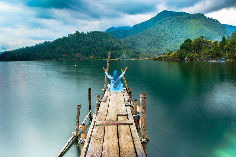 Woman sitting on pier over lake