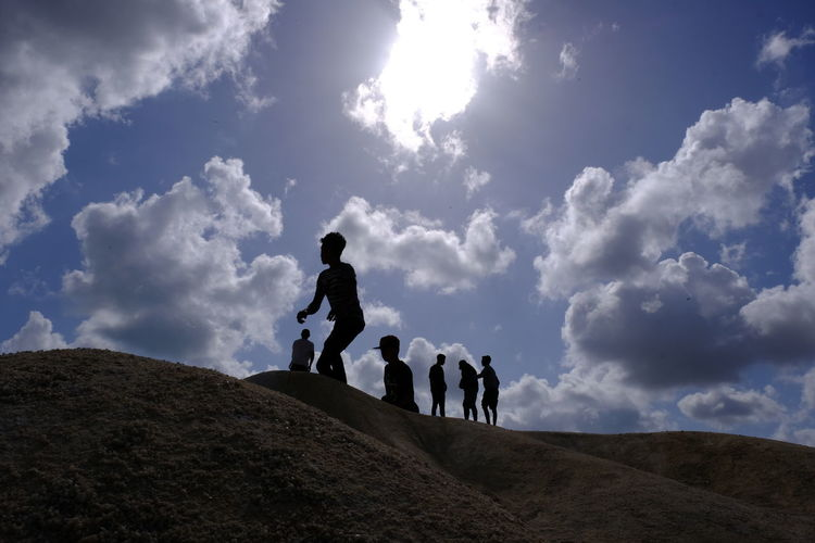 Low angle view of people walking on land against sky