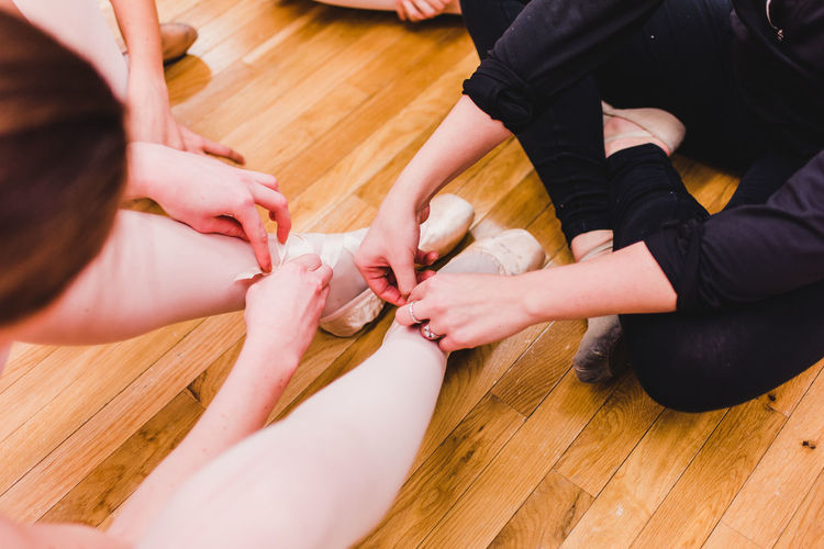 Low section of ballet dancers on hardwood floor