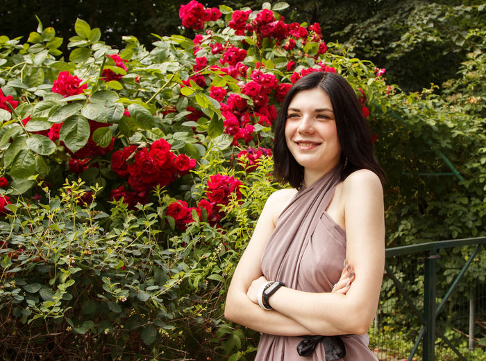Portrait of smiling young woman standing by flowering plants