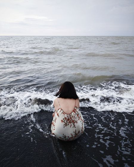 Rear view of woman crouching in sea against sky