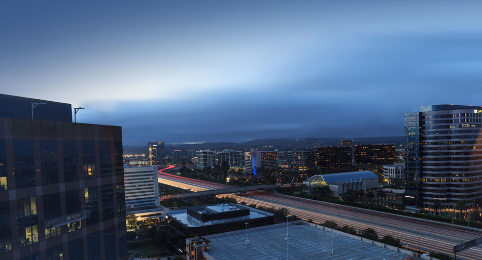 Aerial view of John Wayne Airport in Orange County, California, at sunrise with light trails across the 405 highway in front. Architecture Blue Building Exterior Building Story Built Structure California City City Life City Lights Cityscape Cloud - Sky Financial District  Headlights High Angle View Highway Irvine Mountain Office Building Residential District Sky Skyscraper Tower Urban Scene