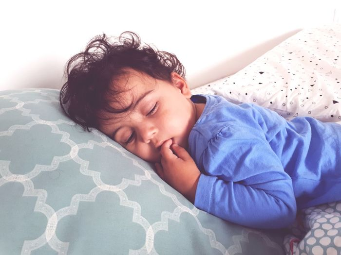 Close-Up Of Cute Baby Sleeping On Bed At Home