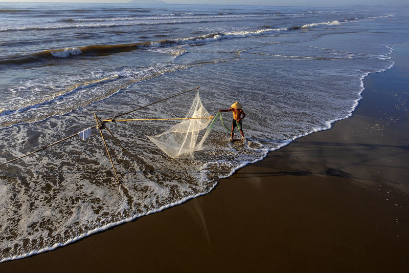 Fisherman Working With Net At Beach