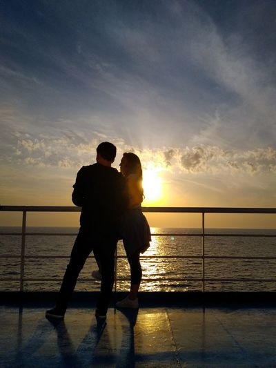 Couple standing on boat deck against sky during sunset